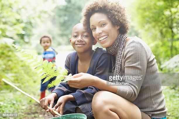 Mère et fils à la recherche de feuille de fougère