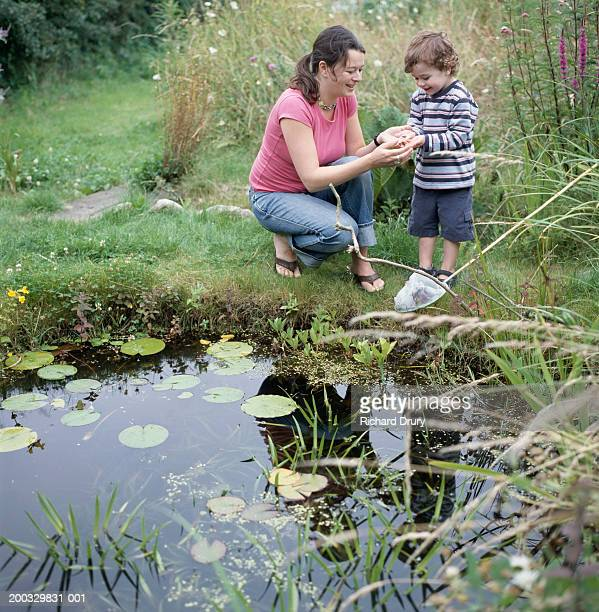 Mother and son (2-4) looking at frog in boy's hand