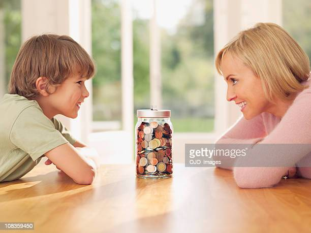 mother and son looking at jar full of coins - mother son shower stock photos and pictures