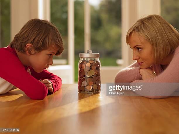 Mutter und Sohn Blick in die Gefäß voll mit Münzen