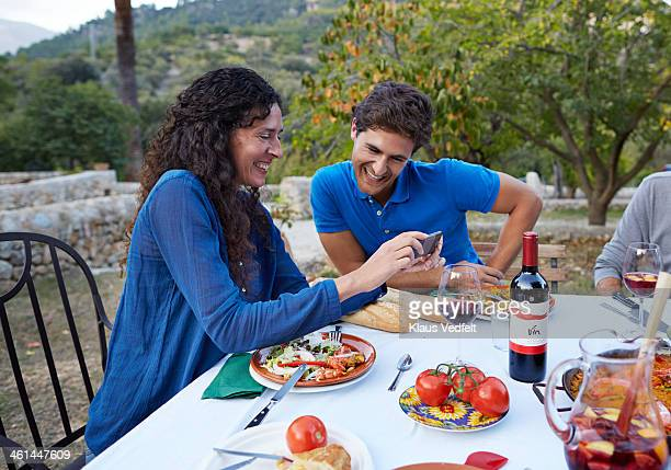 mother and son looking at phone at family dinner - klaus vedfelt mallorca stock pictures, royalty-free photos & images