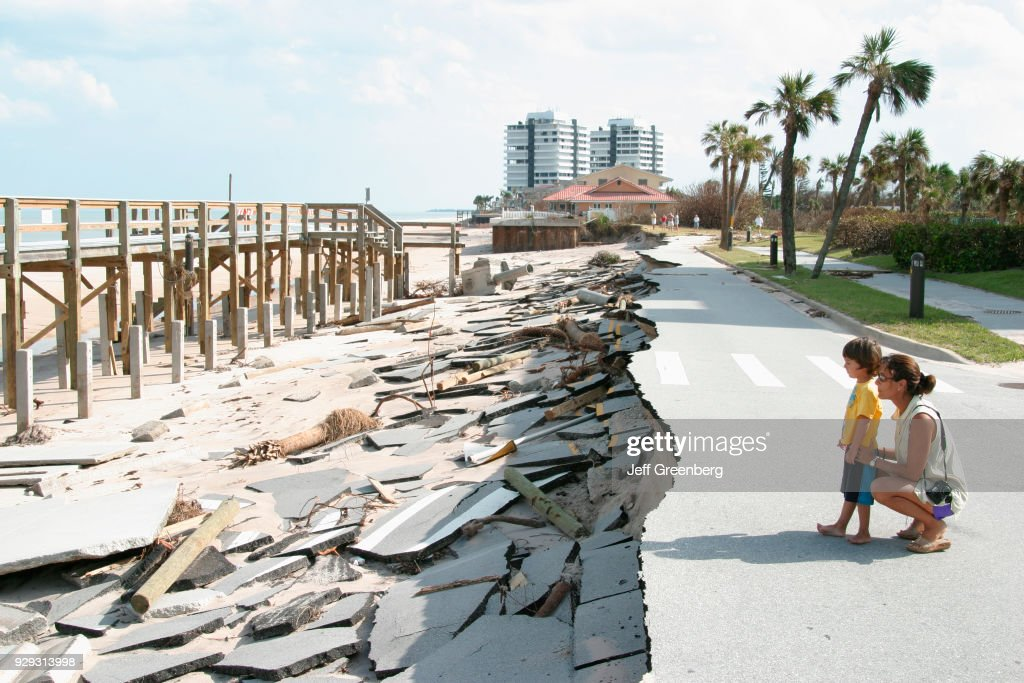 A mother and son looking at the missing road at Vero Beach damaged by Hurricane Jeanne. : News Photo