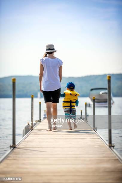 madre e hijo mirando la vista en el muelle en verano - life jacket photos fotografías e imágenes de stock