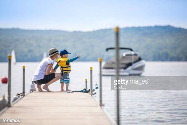mother and son looking at the view on pier in summer - pier stock pictures, royalty-free photos & images