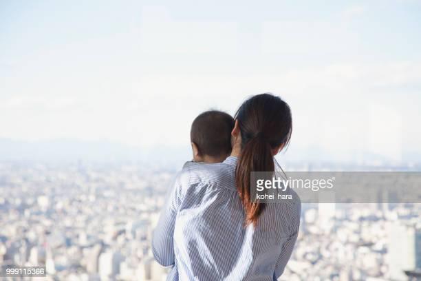 母と息子の高層ビルから街の景色を見て