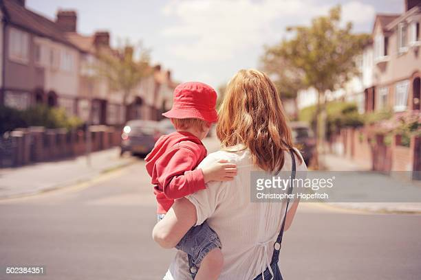 mother and son looking down suburban road - single mother stock pictures, royalty-free photos & images