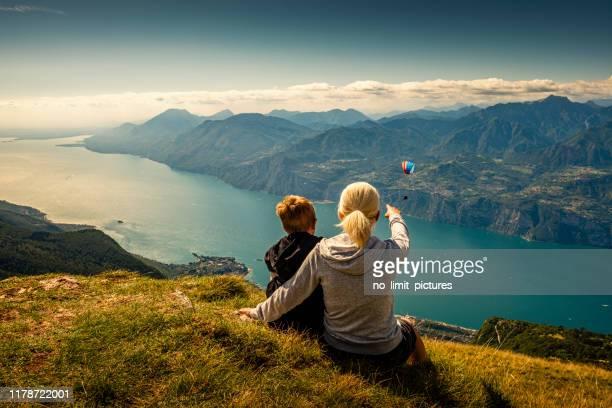 mother and son looking down to lake garda in italy - lago di garda foto e immagini stock