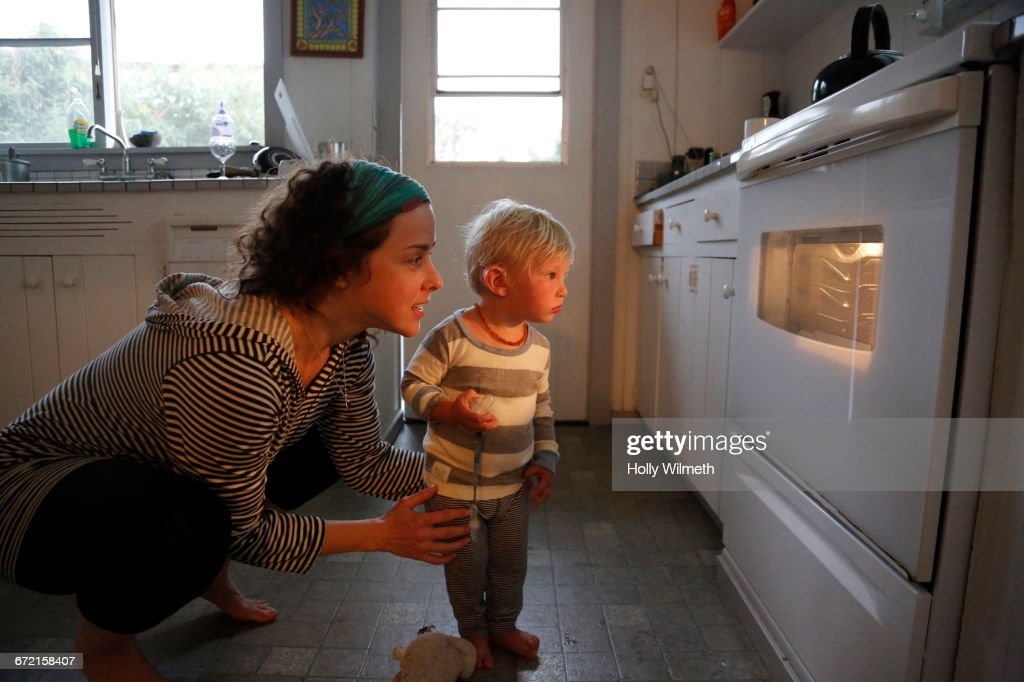 Mother and son looking in oven window : Stock-Foto