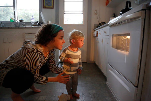 mother and son looking in oven window - 焗 預備食物 個照片及圖片檔