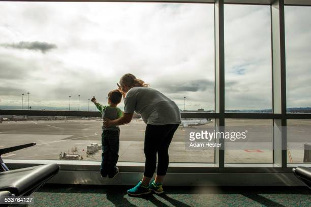 Mother and son looking out airport window