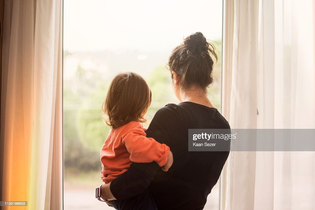 Mother and son looking out of window : Stock Photo