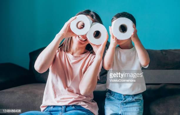 トイレットペーパーのロールを通して見ている母と息子。 - トイレットペーパー ストックフォトと画像