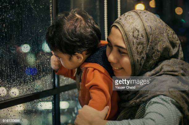mother and son looking through window - mother son shower stock photos and pictures