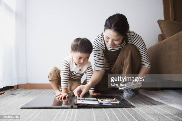 mother and son making a photo album together - rite of passage stock pictures, royalty-free photos & images