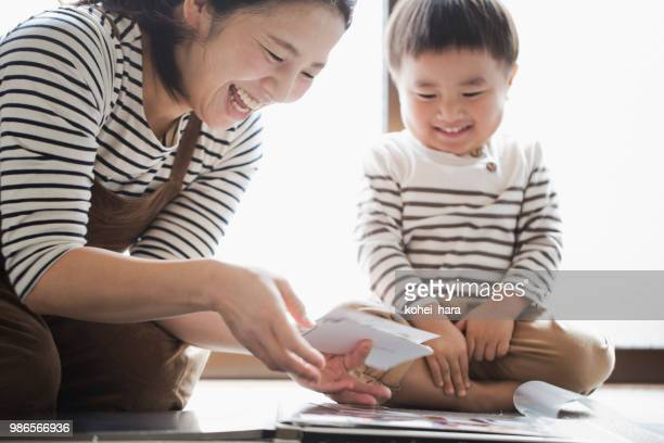 mother and son making a photo album together - childhood photo album stock photos and pictures