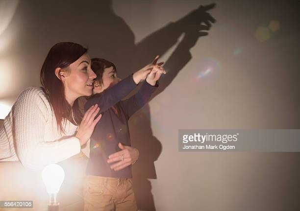 Mother and son making animal shadows on wall