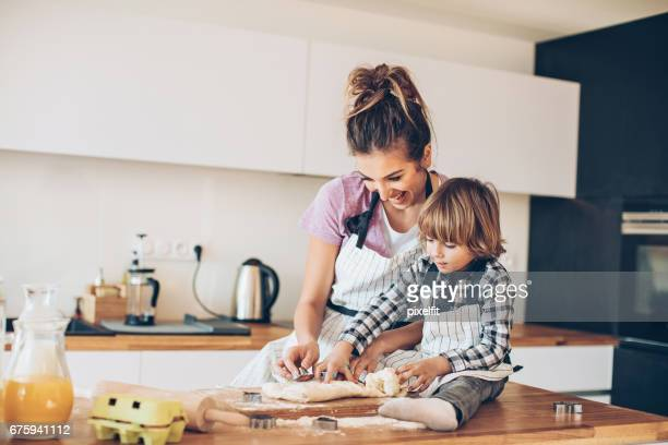 mother and son making cookies together - baked stock pictures, royalty-free photos & images