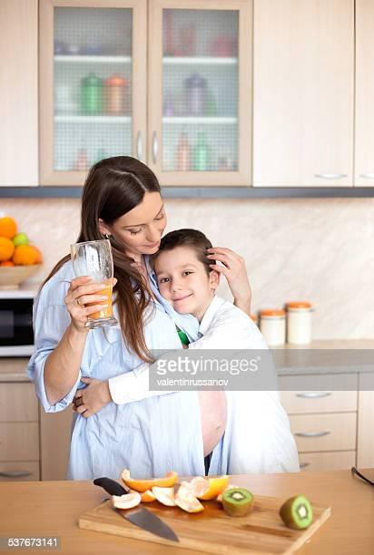Mother and son making fresh orange juice