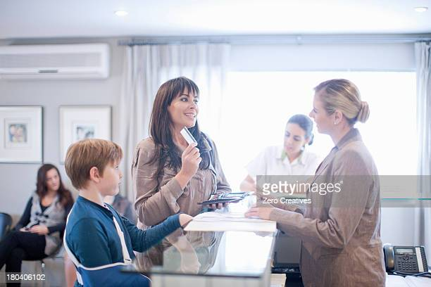 mother and son making payment at hospital reception - medical receptionist uniforms - fotografias e filmes do acervo