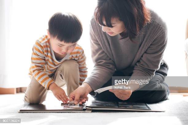 mother and son making photo album - childhood photo album stock photos and pictures