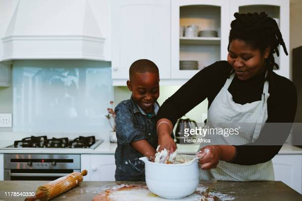 mother and son mix to make dough - family stock pictures, royalty-free photos & images