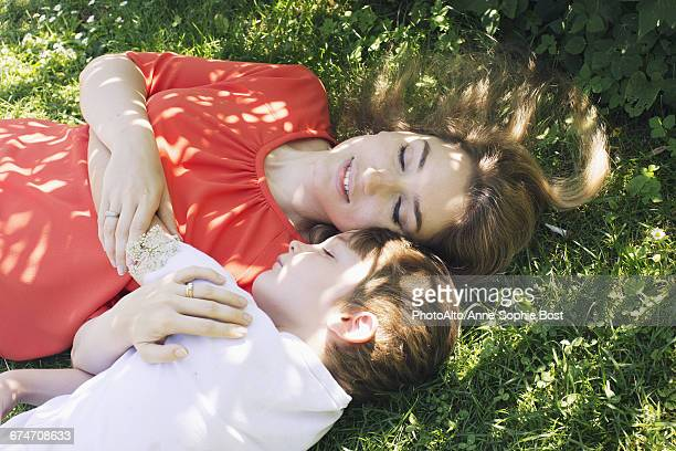 mother and son napping on grass - anne sophie mutter stock-fotos und bilder