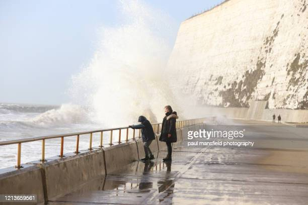mother and son near crashing waves - chalk rock stock pictures, royalty-free photos & images
