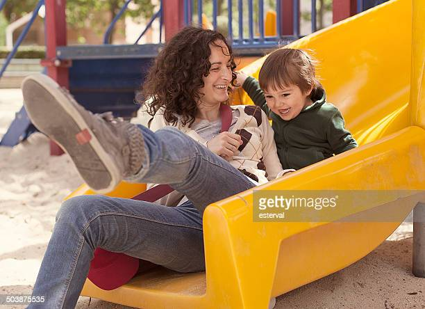 Mother and son on a slide in playground