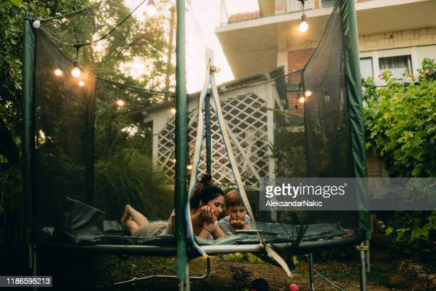 Mother and son on a trampoline, using digital tablet