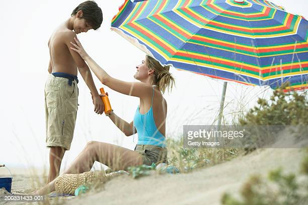 Mother and son (8-10) on beach, mother applying sun cream to son's arm