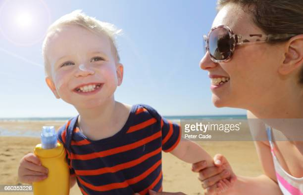 mother and son on beach with suntan lotion - one parent stock pictures, royalty-free photos & images