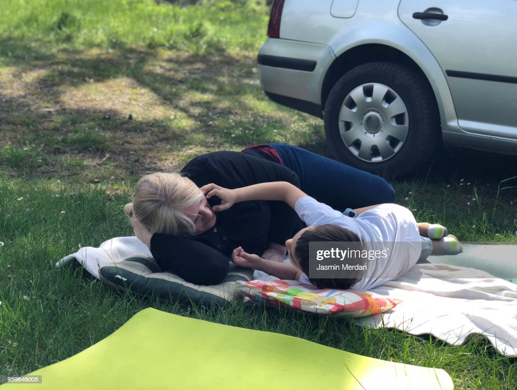 Mother and son on grass during travel : Stock-Foto