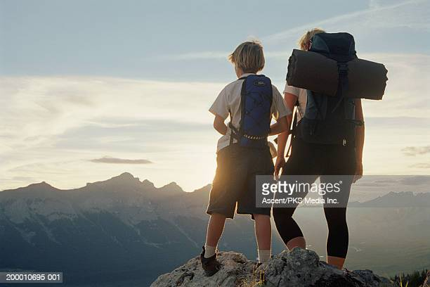 Mother and son (8-10) on mountain top looking at view, rear view