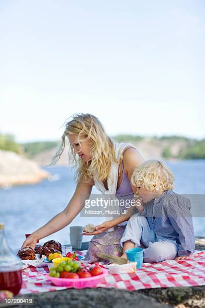 Mother and son on picnic blanket with food beside lake