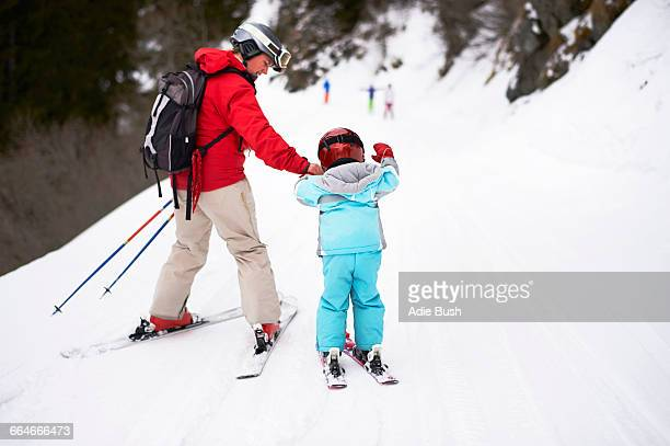 Mother and son on skis, rear view
