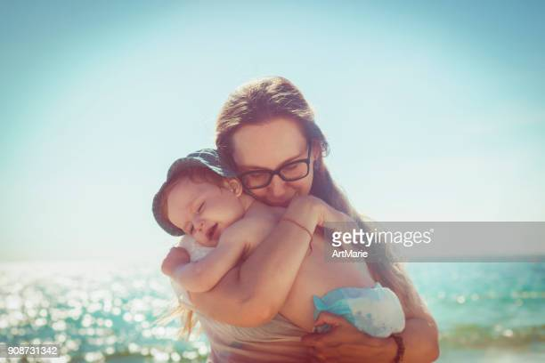 mother and son on the beach - diaper boy stock photos and pictures