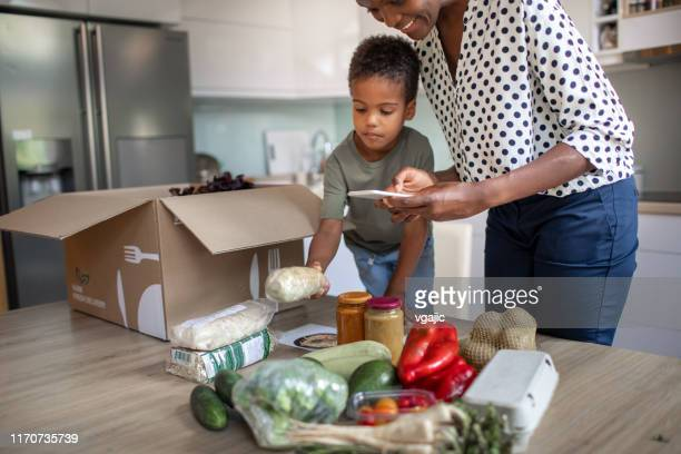 mother and son opening parcel with meal kit - food delivery foto e immagini stock