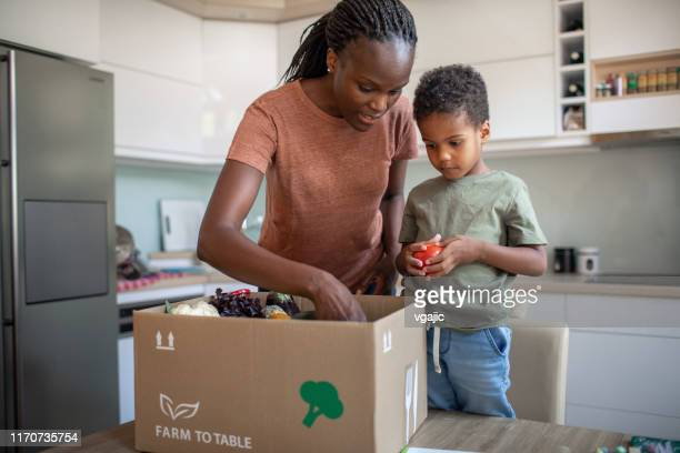 mother and son opening parcel with meal kit - home delivery stock pictures, royalty-free photos & images