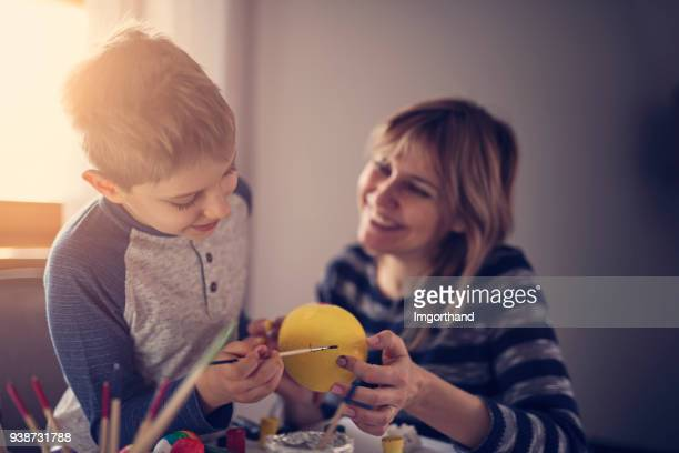 mother and son painting easter eggs - happy easter mom stock pictures, royalty-free photos & images