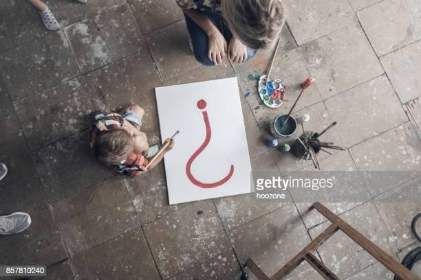 mère et fils, peinture sur toile au sol - objet quotidien photos et images de collection