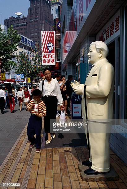 A mother and son pass a statue of Colonel Sanders as they leave Kentucky Fried Chicken with takeout food in Shanghai