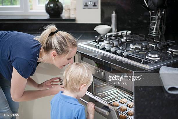 Mother and son peeking in oven to check on baking