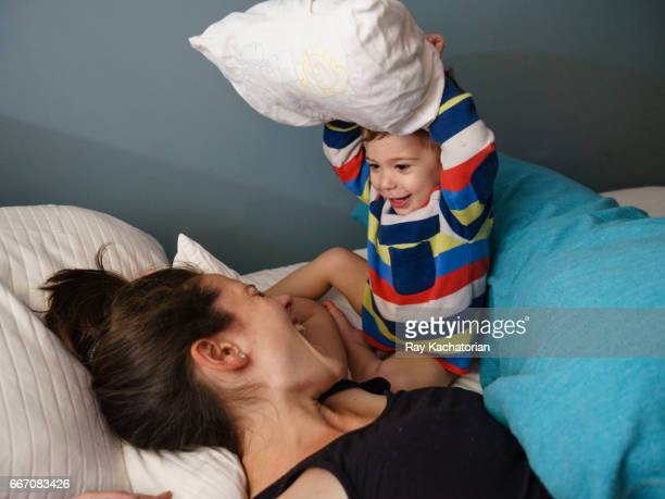mother and son pillow fight - naughty america stock photos and pictures