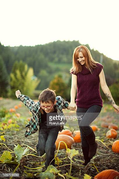 mother and son play in pumpkin patch - leanincollection stock pictures, royalty-free photos & images