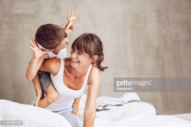 mother and son playfighting in bed, laughing - spielerisch stock-fotos und bilder