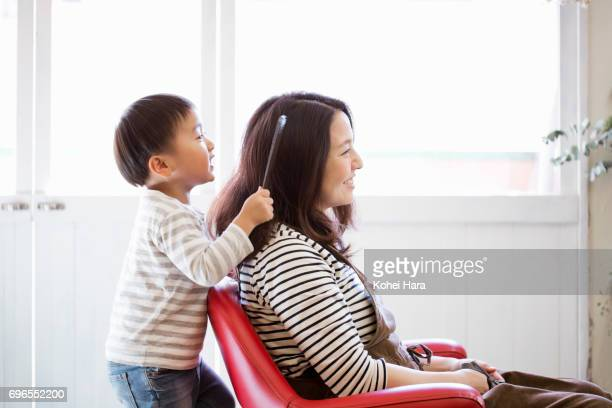 Mother and son playing at beauticians and customers in the hair salon