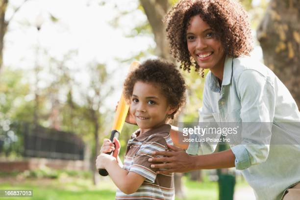 mother and son playing baseball in park - baseball mom stock pictures, royalty-free photos & images