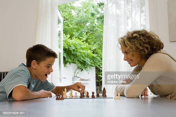 Mother and son (13-15)  playing chess, smiling, side view