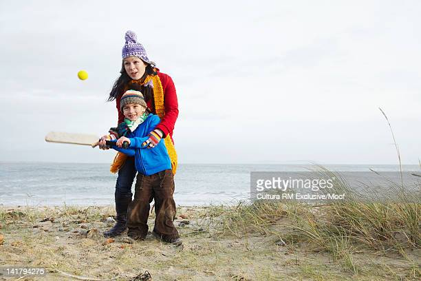 mother and son playing cricket on beach - beach cricket stock pictures, royalty-free photos & images