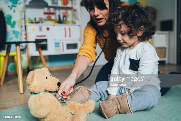 mother and son playing doctor - mama bear stock photos and pictures